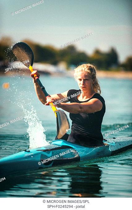 Female kayaker training on lake