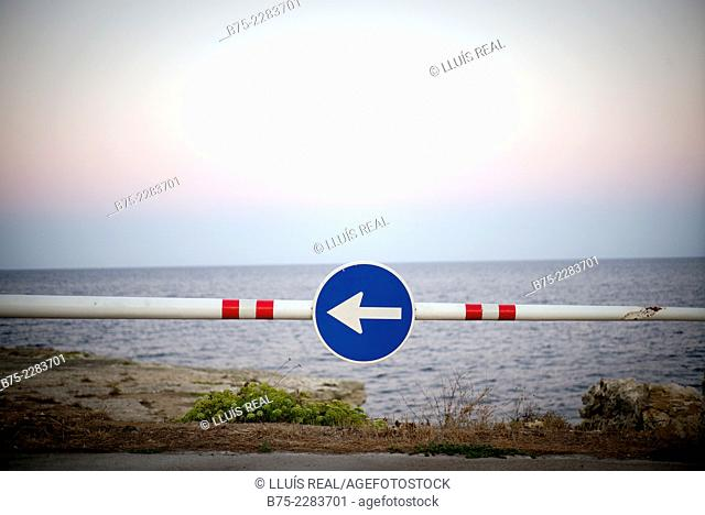 Arrow. Traffic sign direction with the Mediterranean sea in the background in Alcaufar, south coast of Menorca, Balearic Islands, Spain