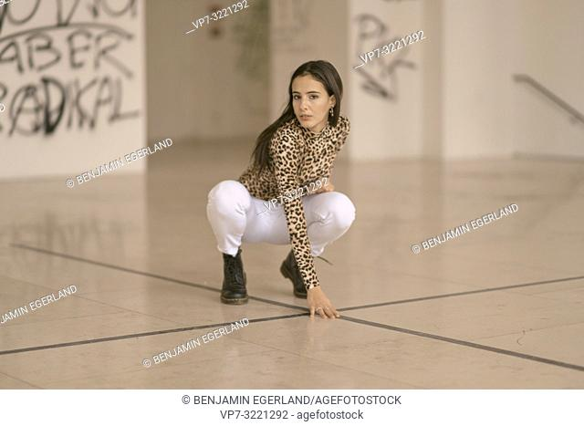 portrait of confident woman performing touchdown on floor, crouching, attentive, wearing fashionable leopard print sweater, in Munich, Germany