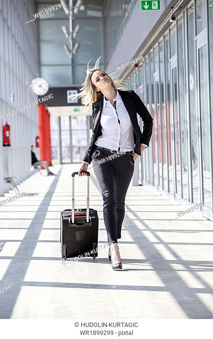 Businesswoman pulling luggage in modern lobby