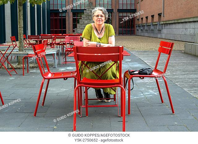 Maastricht, Netherlands. Elder woman sitting on a red colored table and chairs, part of a museum terrace
