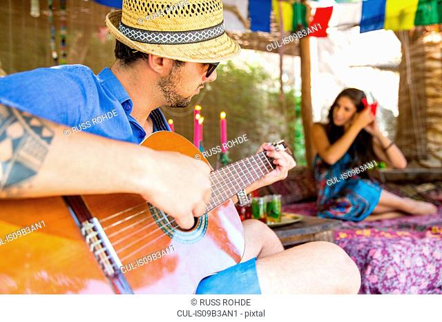 Man playing guitar serenading woman