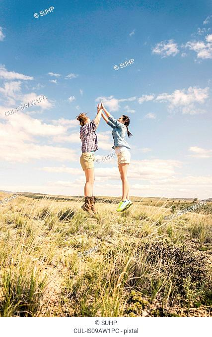 Two young women jumping and high fiving mid air, Bridger, Montana, USA
