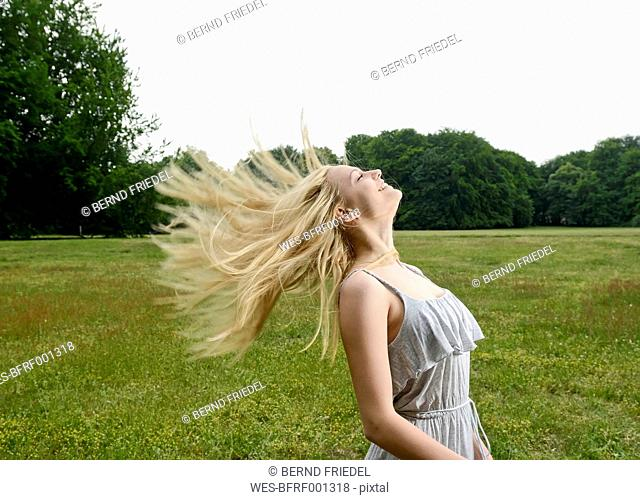 Young woman tossing her hair on a meadow