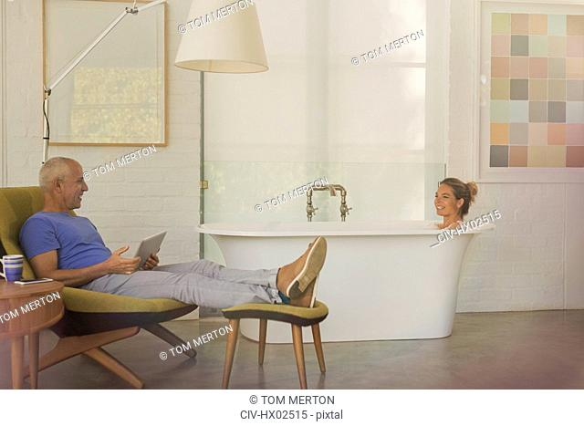 Husband with digital tablet relaxing, talking to wife in soaking tub in luxury hotel room
