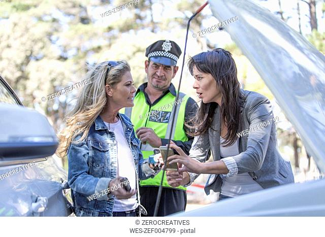 Two women and policeman discussing at car accident scene