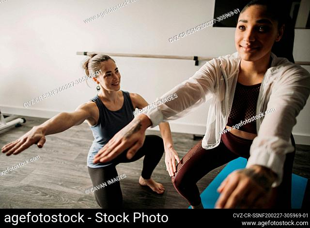Female personal trainer coaches her female student how to squat