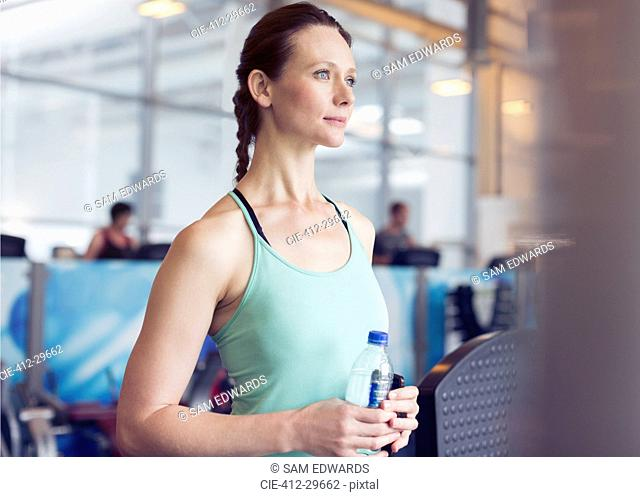 Pensive woman drinking water at gym