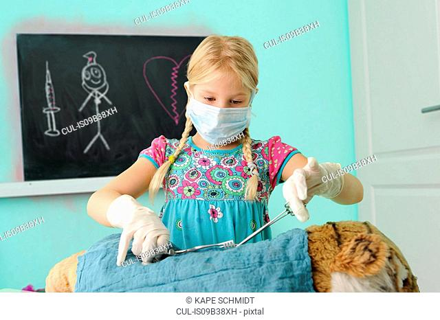 Girl pretending to be vet operating on toy tiger