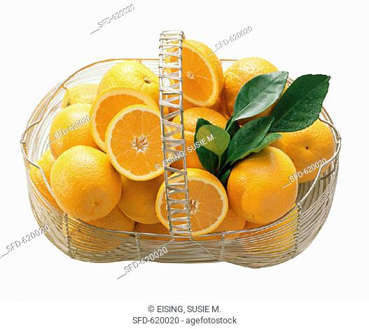 Whole and Halved Oranges in a Wire Basket