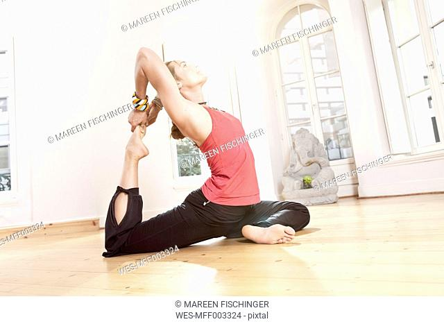 Woman in yoga pose stretching herself