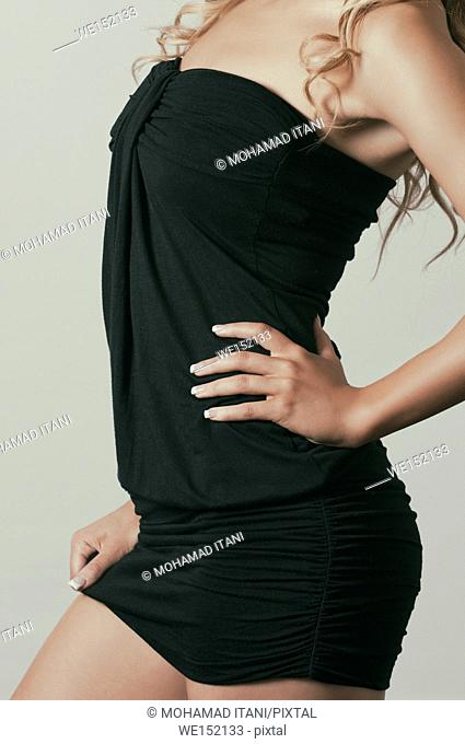 Close up of a sexy young woman wearing a short black dress hand on hips