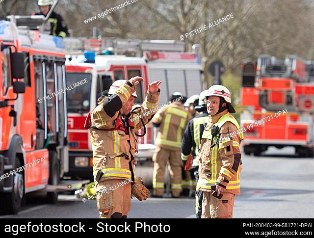 03 April 2020, Berlin: After a fire in Berlin Neu-Hohenschönhausen, firefighters are standing in the street in front of the house and preparing to extinguish it