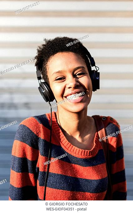 Portrait of laughing young woman listening music with headphones