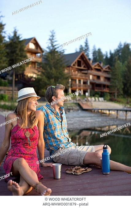 Smiling Young Couple Hanging Out On Dock In Lake Pend Oreille, Sandpoint, Idaho