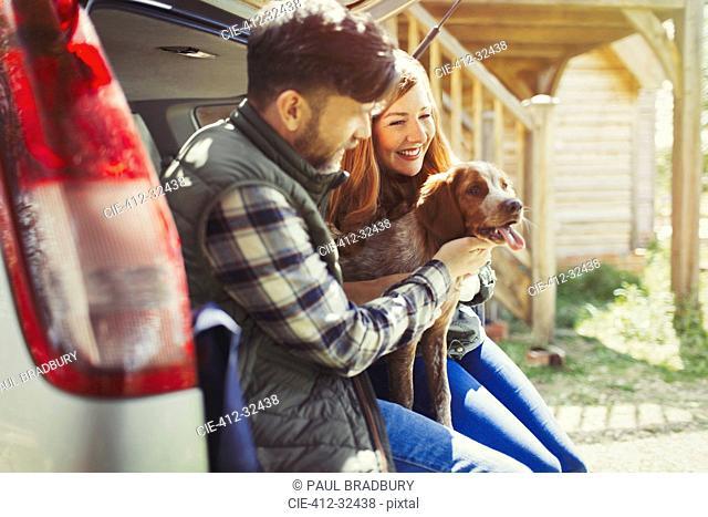 Couple petting pet dog at back of car