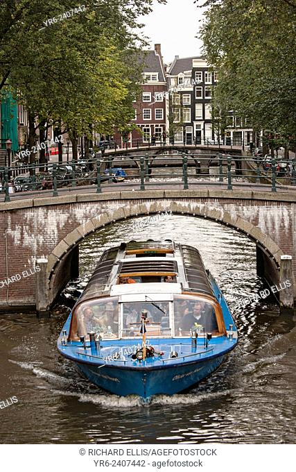 A tour boat passes under the Hemonybrug bridge at Keizersgracht and Leidsegracht in Amsterdam