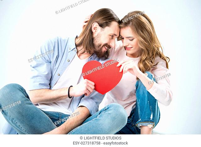 Young happy couple in love holding red paper heart and looking at camera