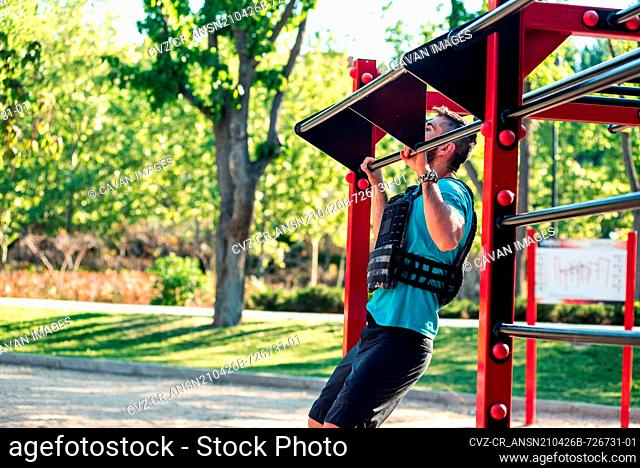 Side view of a bearded brunette man doing a barbell pull-up with weight vest. Outdoor fitness concept