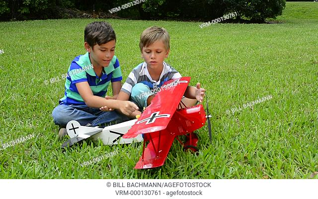 Two young boys playing with a model plane German Fokker DII from WWI in the yard at home MR-12 MR- 13 Model released