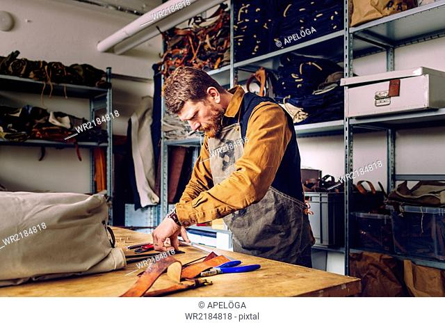 Male worker manufacturing bag at worktable in factory