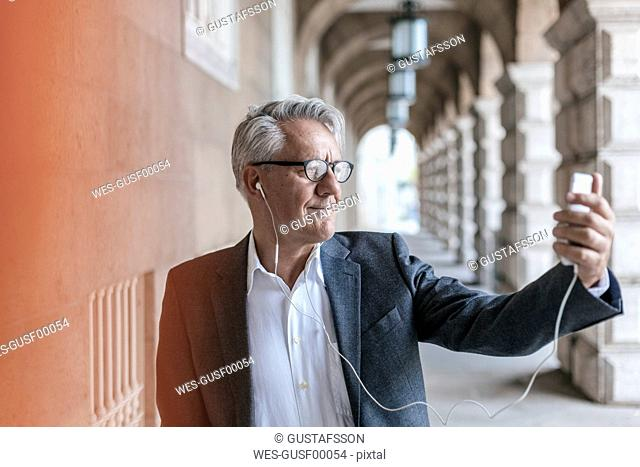 Portrait of smiling senior businessman taking selfie with smartphone