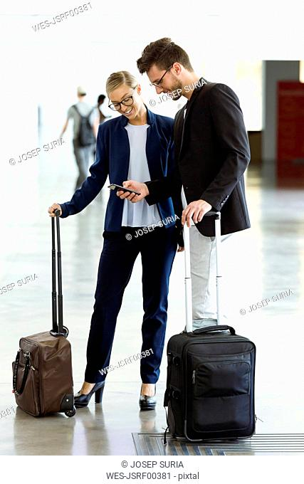 Two smiling young business partners using a smartphone at the airport