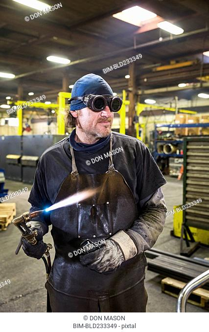 Caucasian welder holding blowtorch in factory