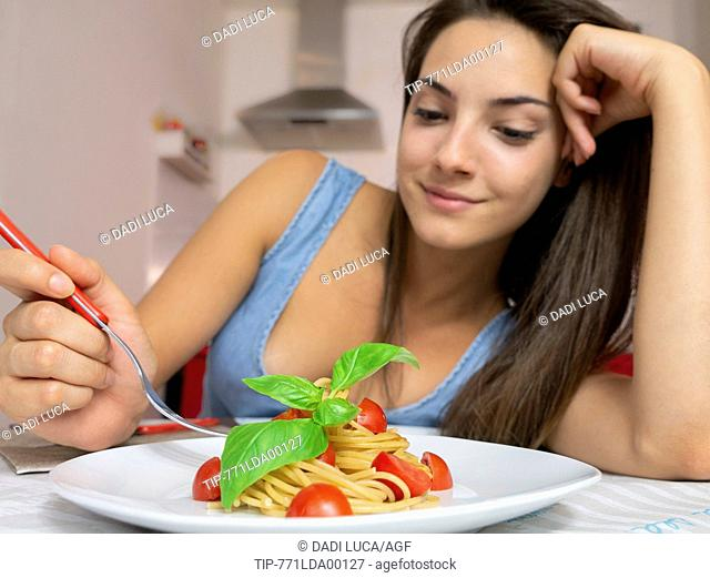 young woman eating wholemeal spaghetti with tomatoes and basil