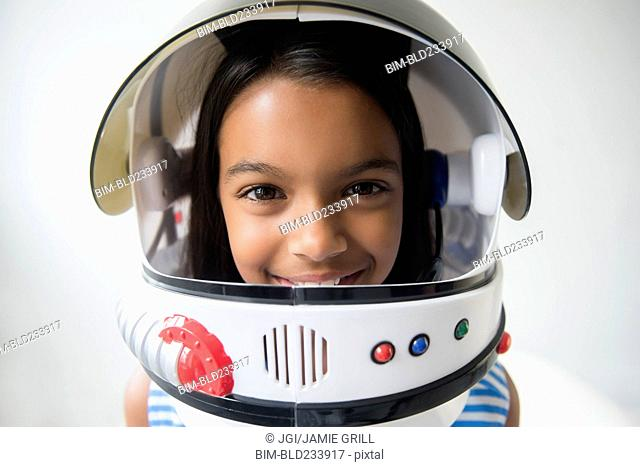 Mixed Race girl wearing astronaut helmet