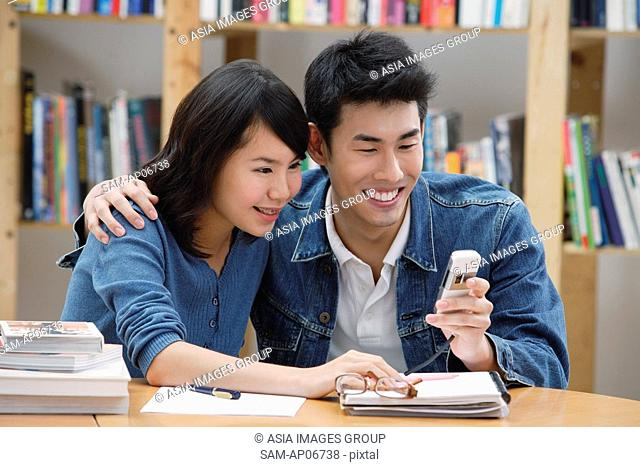 Couple in library, looking at mobile phone