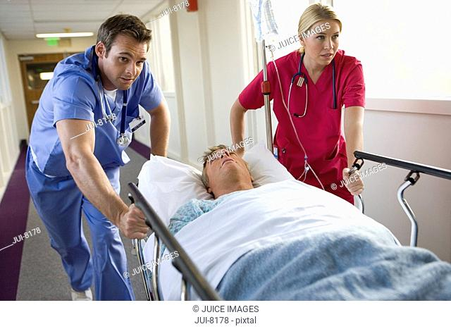 Male and female doctors pushing mature male patient lying on hospital bed in corridor