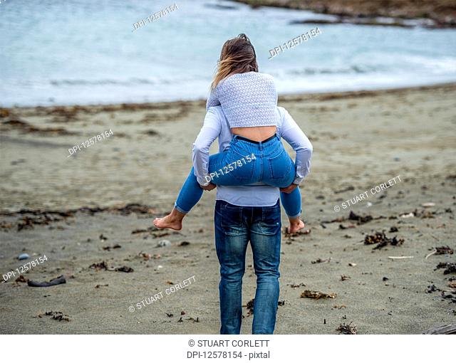 A young couple at the beach, the young woman being carried on the young man's back; Wellington, North Island, New Zealand