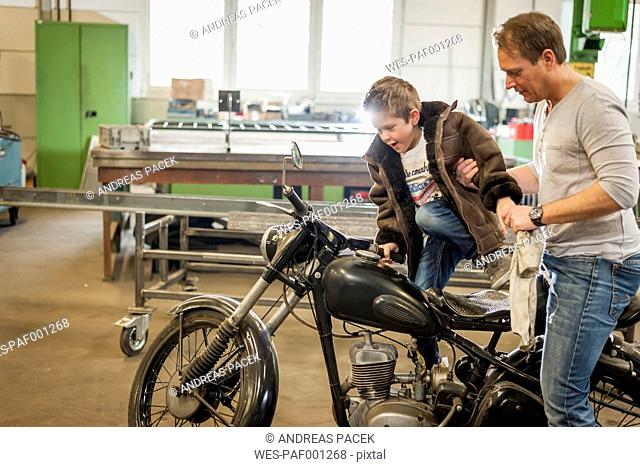 Father and son maintaining vintage moped