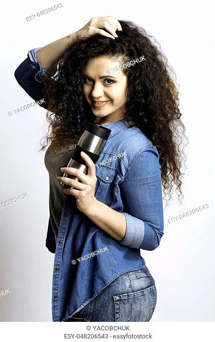 Lets drink. Effective young girl touching her hair holding a thermos looking at camera
