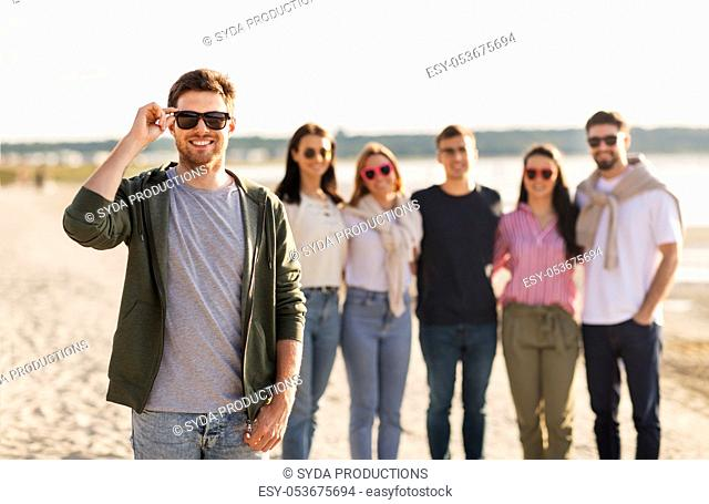 man in sunglasses with friends on beach in summer
