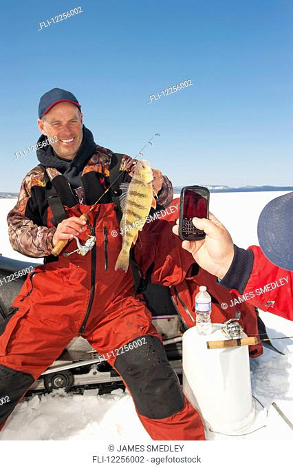 Woman taking a cell phone picture of an ice fisherman holding a winter walleye catch; Ontario, Canada