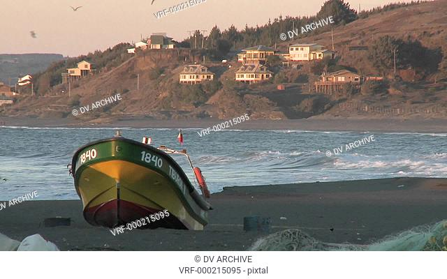 A fishing boat and surfer on the beach at Curanipe, Chile