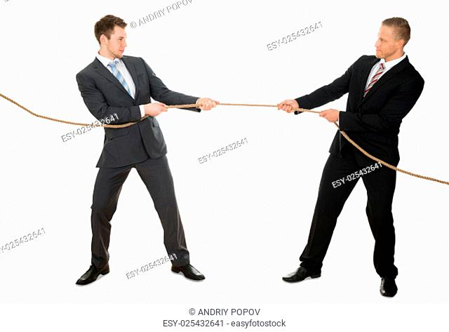 Portrait Of Two Businessman Pulling Rope Over White Background