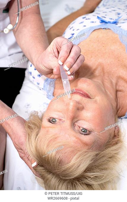 Nurse administering nasal drops into a patients nose
