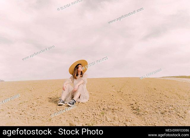 Woman with straw hat and vintage dress sitting on a remote field in the countryside
