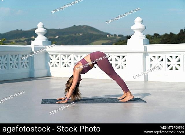 Young woman practicing downward facing dog position on building terrace