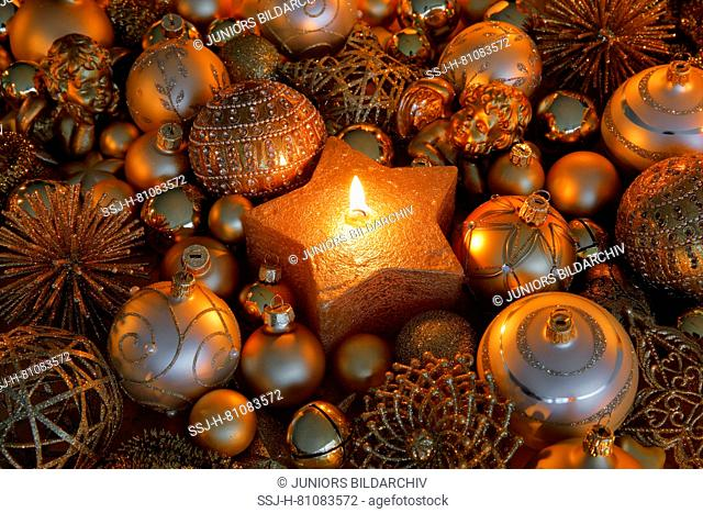 Golden Christmas baubles and burning tealight in a star-shaped candle holder. Studio picture. Switzerland