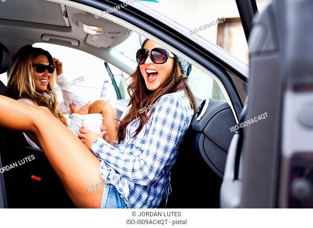 Two female friends in car with takeaway drinks