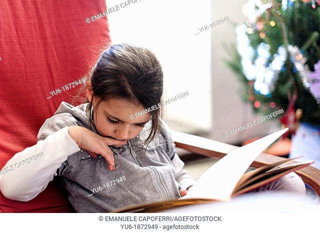 Little girl reading a book sitting on red chair, next to the Christmas tree
