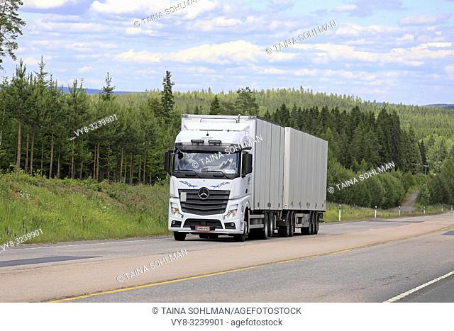 Jamsa, Finland - June 14, 2018: White Mercedes-Benz Actros freight truck pulls trailer uphill on scenic highway on a beautiful day of summer