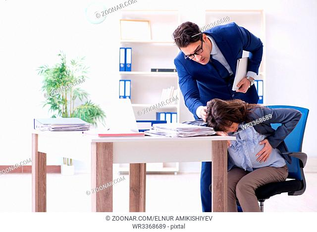 Pregnant woman struggling in the office and getting colleague help