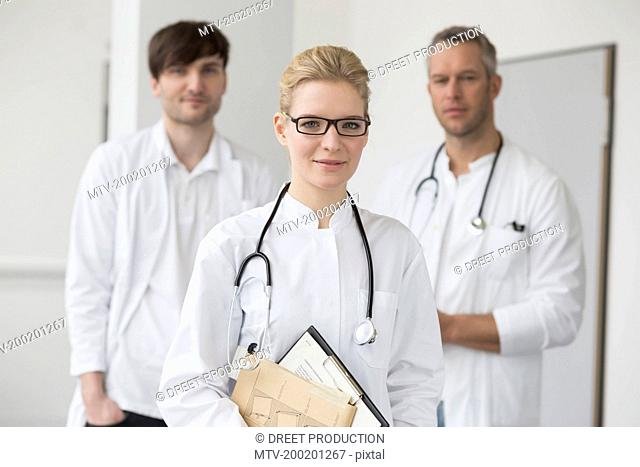 Female doctor with file while colleagues in background