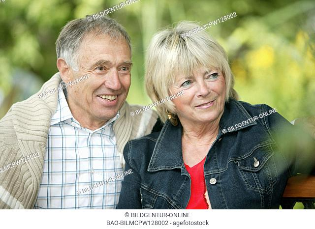 elderly couple senior citizens sitting on a bench in the garden
