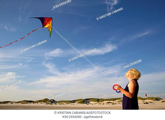 Young caucasian woman with kite at the beach and a lighthouse in the background, Amrum, Northfrisian, Schleswig-Holstein, Germany, Europe